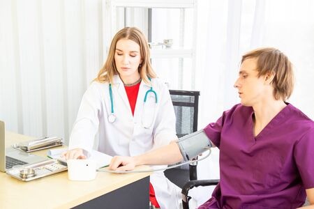 Ethnicity Caucasian Male patients come to a female doctor measured the pressure with a pressure gauge to check the health in the examination room, backdrop of white curtains in the hospital or clinic.