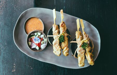Chicken satay or Chicken kebab skewers on a black ceramic plate with side dishes made from cucumbers, red onions, peppers and Thai dipping sauce.