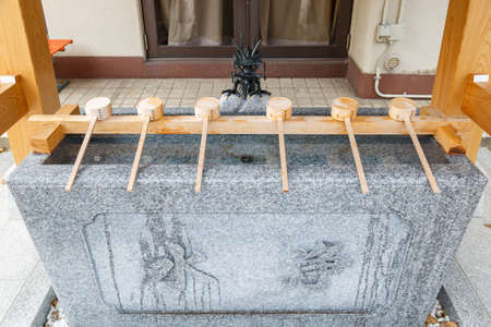 Water ladle made of wood and pond in front of Shinto shrine for washing hand and gargle mouth before entering the shrine. Editorial