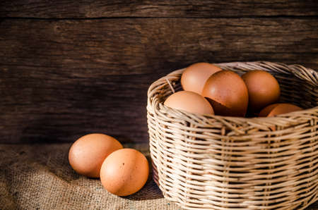 Still life concept many eggs in basket with old wooden background photo