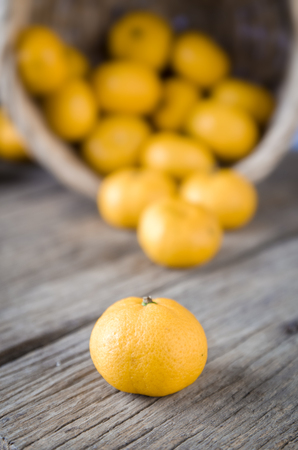 small bowel: Closeup fruits. yellow oranges pouring on wooden floor