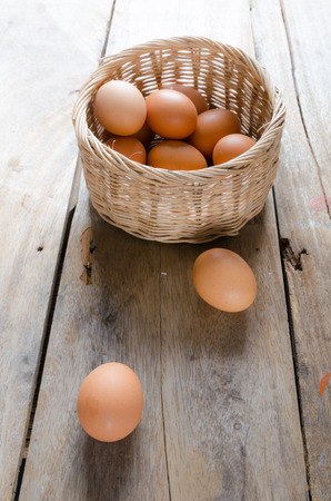 Front and top shot of eggs with basket on wooden floor photo