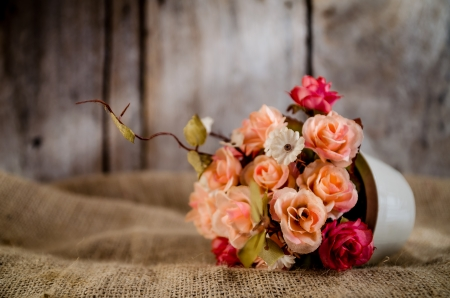 vase color: Vintage tone color of artificial flowers on sack with wooden