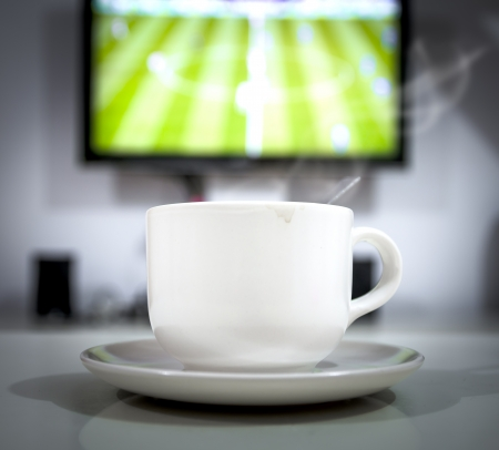 coffee time: closeup of coffee cup in front of the TV. It is a football live time.