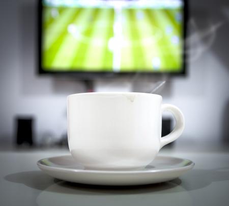 tasse de caf�: Gros plan sur la tasse de caf� en face de la TV. C'est un ballon de football en direct de temps.