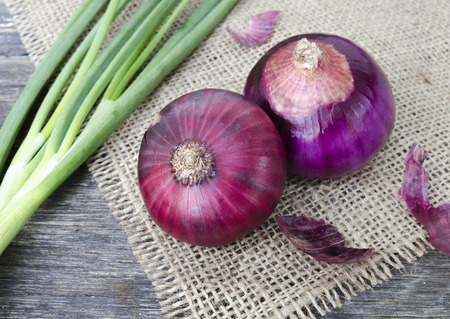 close-up red onion and leaves on sackcloth. still-life photo