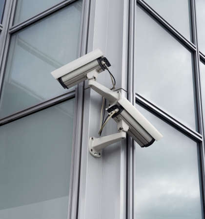 Two security cameras attached on building corner photo