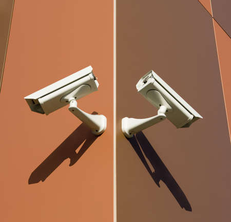 attached: Two security cameras attached on building corner