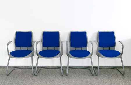 Vier blauen Stühlen im einfachen leeren Wartezimmer