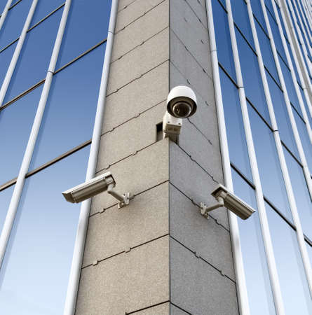 Three security cameras attached on the office building corner photo