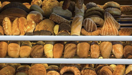 Set of different breads on the bakery shelf photo