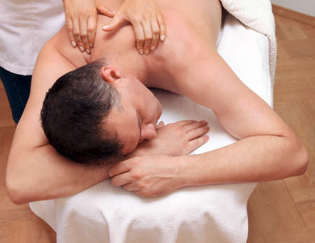 massaged: Man getting a relaxing massage in spa salon Stock Photo