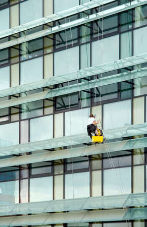 Window washer hanging outside facade photo