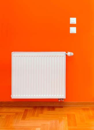 warmness: Radiator heater attached on the orange wall Stock Photo