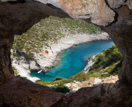 cave exploring: View from cave on small boat in cove
