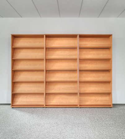灰色の壁に空の木製の本棚