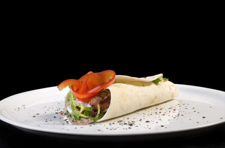 Traditional Turkish Kebab Tortila on Plate Isolated on Black Background photo