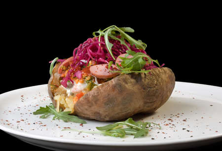 Stuffed Baked Potato on White Plate Isolated on Black Background photo