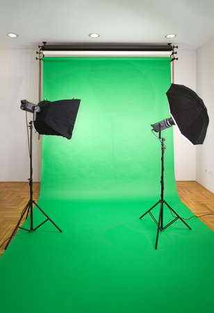 strobe: Empty Photo Studio with Lights and Green Backdrop Stock Photo