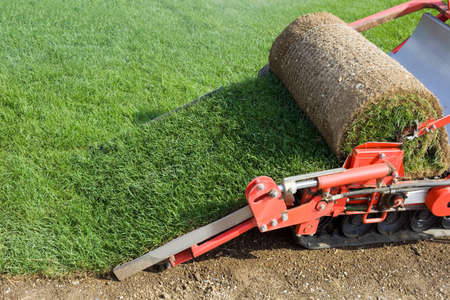 sod: Circular Grass Carpet Cutting Baling Machine Stock Photo