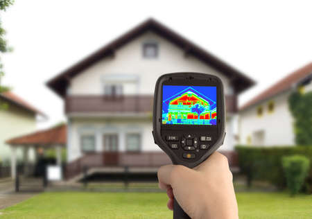 eficiencia energética: Detección de pérdida de calor de la casa con cámara térmica de infrarrojos Foto de archivo