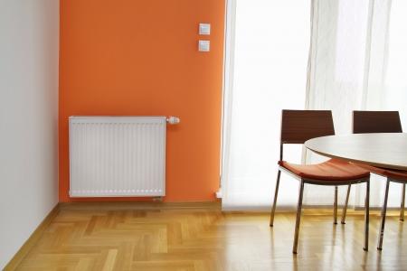 Readiator riscaldamento sul Orange Wall Archivio Fotografico - 22980448