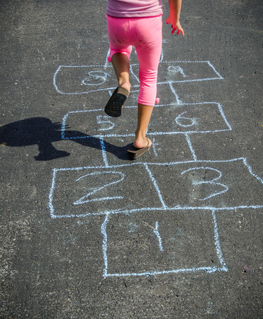 wearing sandals: Child Skipping While Playing Hopscotch Outside on a Sunny Day Wearing Sandals