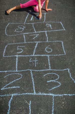 hopscotch: Girl Drawing with Chalk Outside Playing Hopscotch