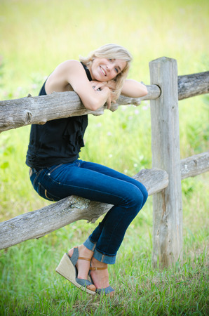 blonde teenage girl: Blonde Teenage Girl Wearing Jeans Leans on Wooden Fence with Grass and Field in Background Stock Photo