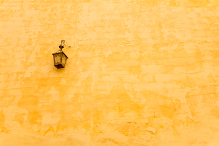 An antique lamp and yellow wall. Banco de Imagens