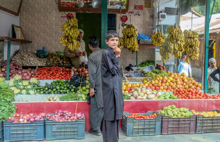 Khyber Pakhtunkhwa, Pakistan. October 14, 2015 : A man selling fruits and vegetables to customer at a local grocery shop.