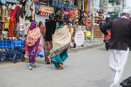 Murree, Pakistan. October 15, 2015 : Pakistani people in traditional dress walking at the shopping street.