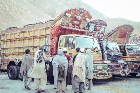 Sost, Pakistan. October 9, 2015 : Pakistani men are talking near their beautiful decorated trucks.