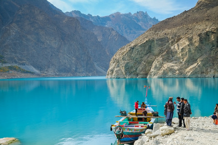 Gilgit Baltistan, Pakistan. October 28,2017 : People going to rent a boat at Attabad lake, with a view of mountains backdrop. Gojal, Hunza, Pakistan.