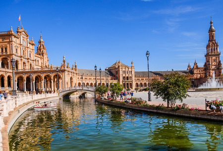 Tourists enjoy sightseeing and boating in a canal at the Plaza de España. Seville, Spain.