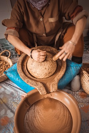 Moroccan woman grinding argan kernels into thick brown oily liquid. Essaouira, Morocco.