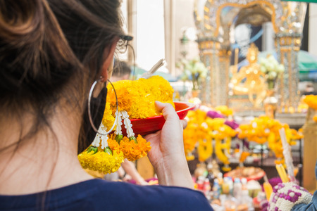 A woman make ceremonial offerings from floral garlands at the Erawan Shrine in Bangkok, Thailand. Stock Photo