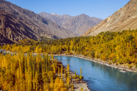 Gahkuch in autumn show river flow through colorful forest and surrounded by mountains in karakoram range. Ghizer, Gilgit Baltistan, Pakistan.