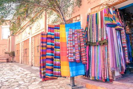 Colorful traditional Moroccan scarves and shawls hanging on a tree for sale at a souvenir shop in Ouarzazate, Morocco.