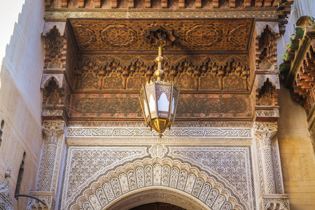 Beautiful ancient Moroccan art decoration in the city of Fez. Wooden carved ceiling, antique lamp and arabesque art on the wall. Fes el Bali, Morocco.