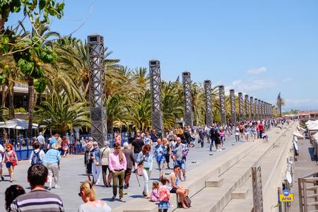 Barcelona, Spain. May 8, 2017 : People walking along a marina bay near the beach in Barcelona.