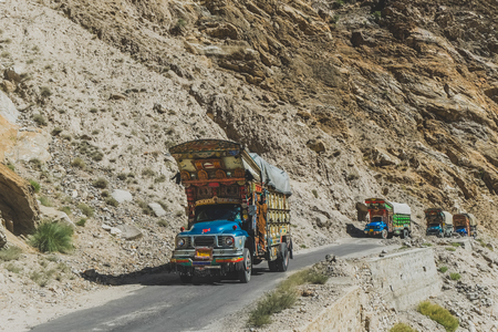 Gilgit Baltistan, Pakistan. October 11, 2015 : Pakistani decorated trucks travelling on paved road, transport goods via Karakoram highway along the mountain. Editorial