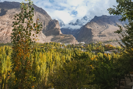 Beautiful scenery panoramic view in Hunza valley. Nature landscape of lush green forest with clouds covered snow capped Ultar Sar mountain in Karakoram range, Karimabad, Gilgit Baltistan, Pakistan.