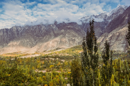Nature landscape view in Hunza valley. Beautiful scenery of green forest with clouds covered snow capped mountain peaks in Karakoram range, and blue sky in the background. Gilgit Baltistan, Pakistan.