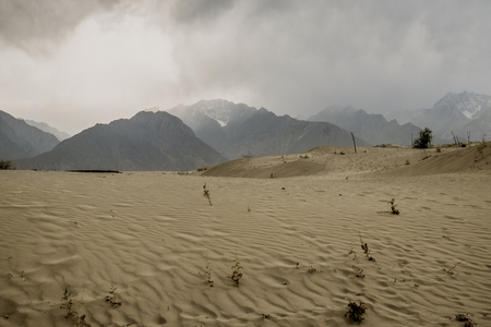 Cloudy and dusty scene after storm. Nature scenery in Katpana cold desert with snow capped mountains in karakoram range, Skardu. Gilgit Baltistan, Pakistan. Imagens