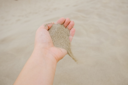 Sand flowing from a hand into the desert.