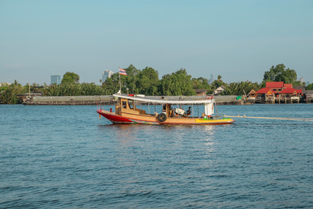 A local wooden boat with Thai flag in Chao Phraya river, Thailand. Banco de Imagens