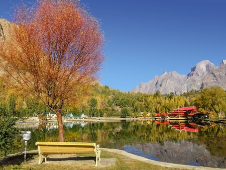 Colorful foliage in autumn with reflection in the water of trees and mountains in Karakoram range at lower Kachura Lake. Beautiful scenery in Skardu. Gilgit Baltistan, Pakistan.
