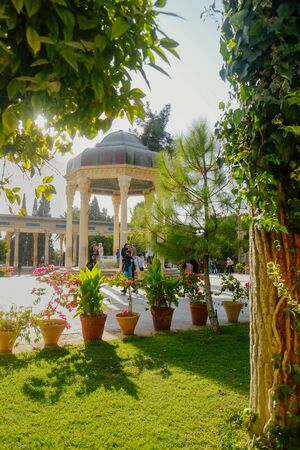 Shiraz, Iran. October 24 2016 : The pavilion over the Tomb of Persian poet Hafez surrounded by lush green garden.