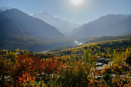 Morning natural sunlight lit colorful foliage trees in forest and mountains in Karakoram range in the background. Hunza Nagar valley in autumn season. Gilgit Baltistan, Pakistan.